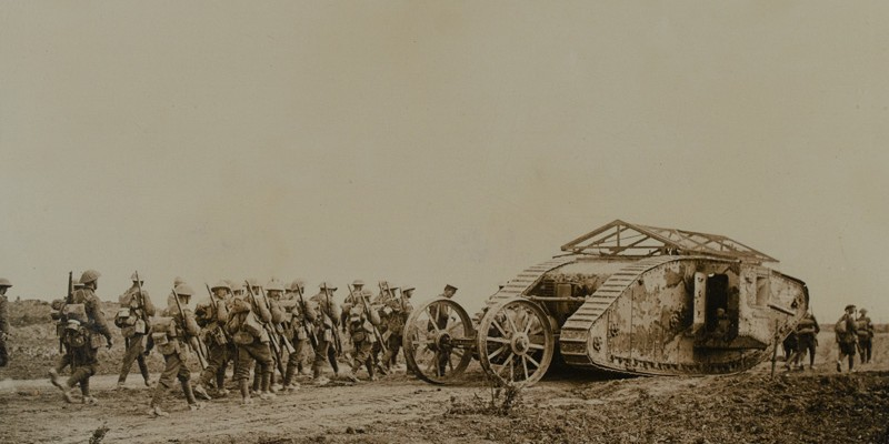 A Mark I tank with grenade screens and rear steering wheel device advances with infantry marching behind, 1916