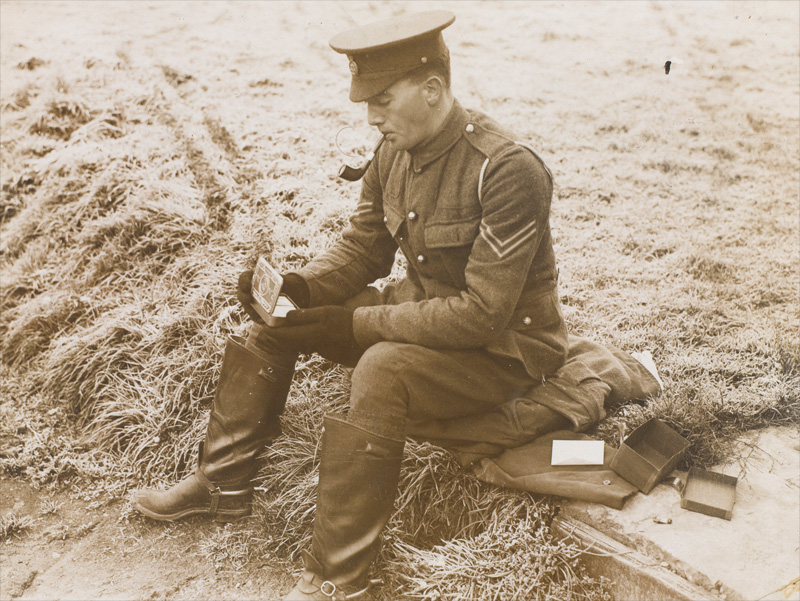 A soldier opening his Princess Mary gift tin, 1914