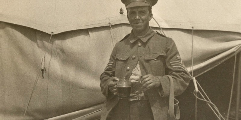 Sergeant Archie Favell stands outside a tent, which possibly contains some of the supplies for which he was now responsible