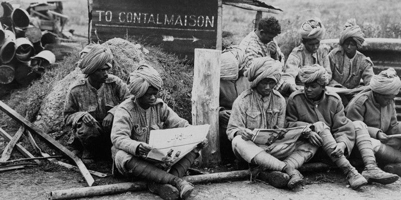 Members of an Indian Labour Battalion reading papers during a work break, c1917
