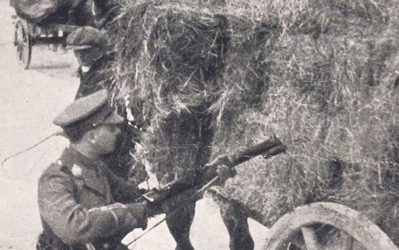 Photograph of a British officer searching a hay cart for rebels or ammunition with a rifle and bayonet, May 1916