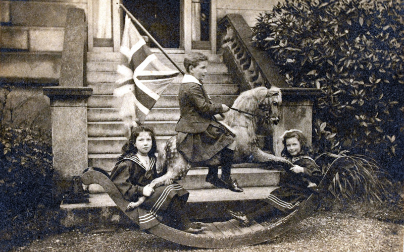 Douglas McKie and his sisters, Helen and Katharine, playing on a rocking horse, 1900