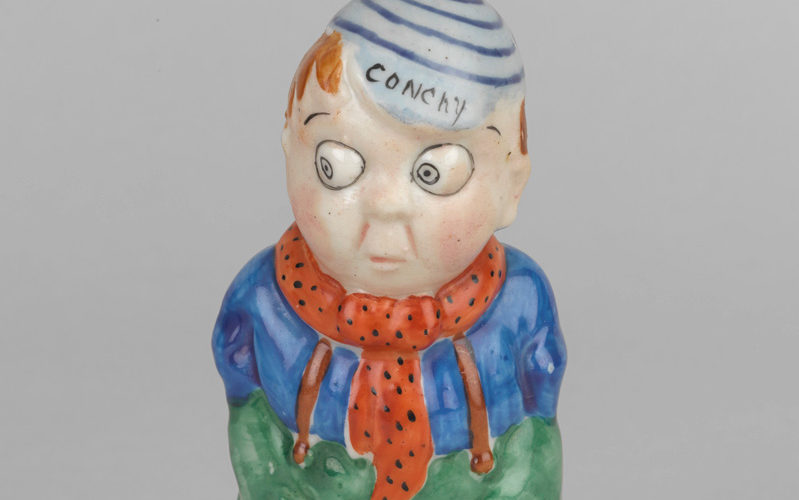'Conchy' - a satirical ceramic figure from around 1916, criticising conscientious objection. The figure has his hands in his pockets, which for a soldier, is a disruption of army discipline.