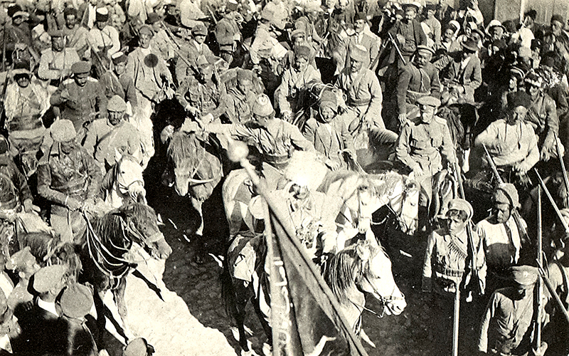 Assyrian troops led by Agha Petros (saluting) with a captured Turkish banner in the foreground, 1918