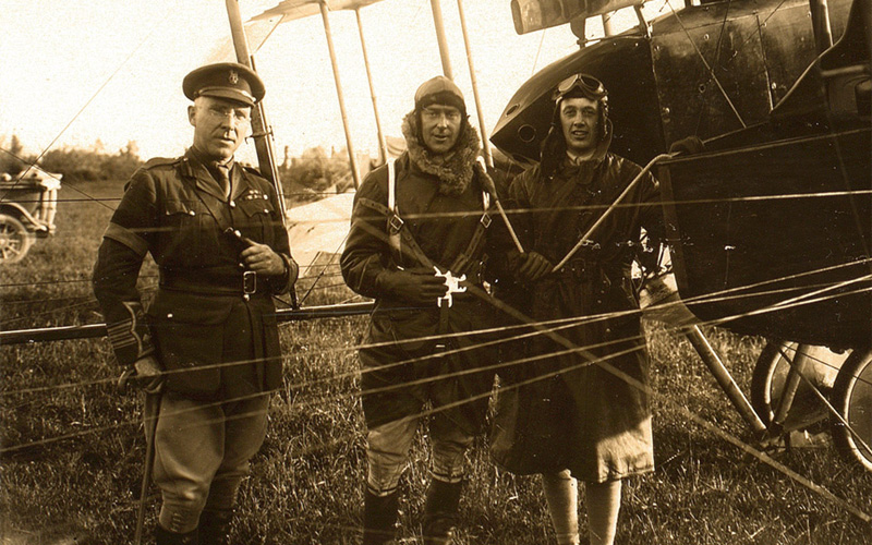 Captain Bowen (centre) wearing the parachute harness before the drop on 26 June 1918. To his left is Lieutenant-Colonel Billy Mitchell of the United States Army Air Service.