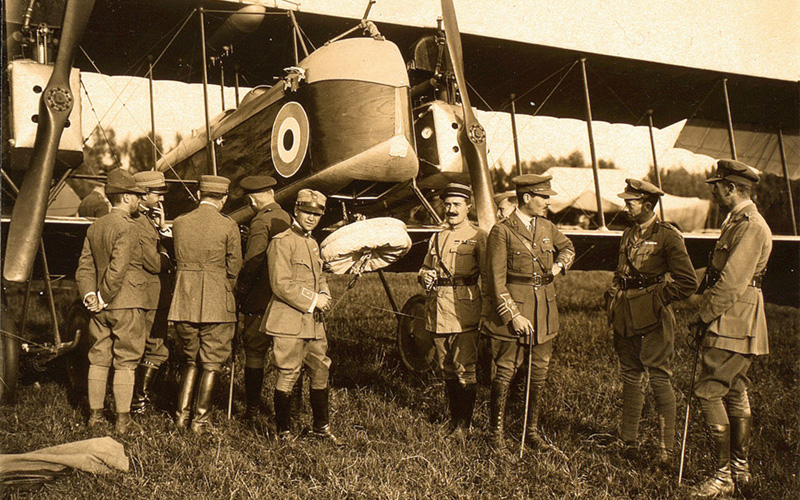The parachute tied up under the forward observer's seat with British and Italian officers looking on, 26 June 1918